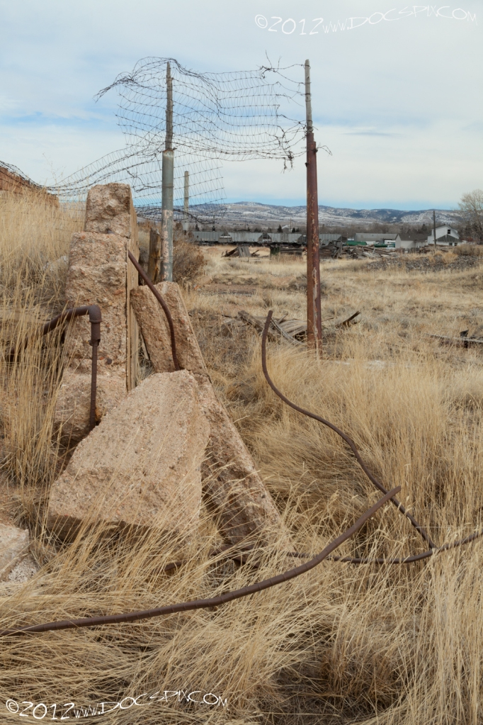 A wider view of the rebar on the pipe. Remnants of an old fence can be seen in the background.