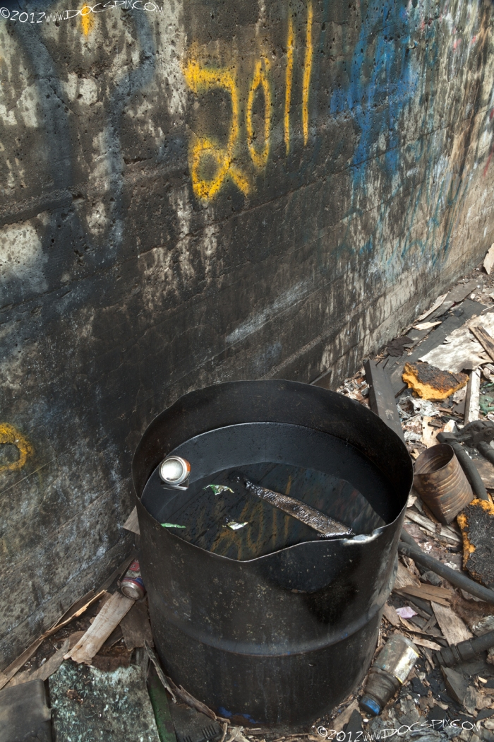 A half-oil drum sits next to the north wall of the factory floor.