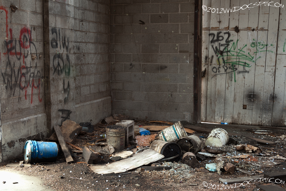 A number of oil containers and debris occupy the south west corner of the factory floor.