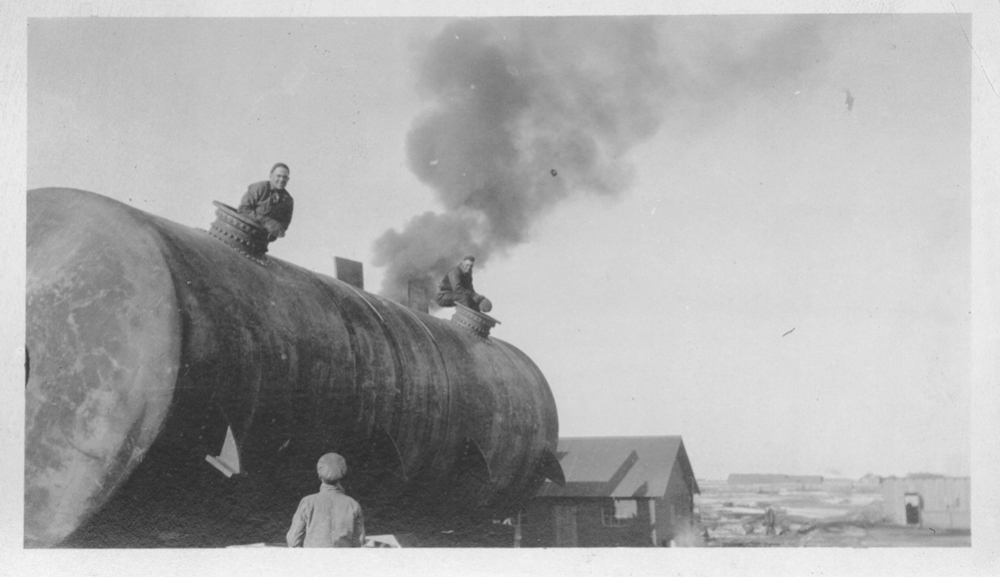 A pair of workers sit on top of one of the tanks that would be placed on top of the foundations. (Courtesy of the American Heritage Center, University of Wyoming, digital collections)