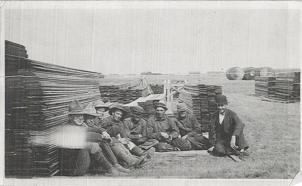 A group of men sit near stacks of lumber that would be used as concrete forms. Note the tanks in the background.