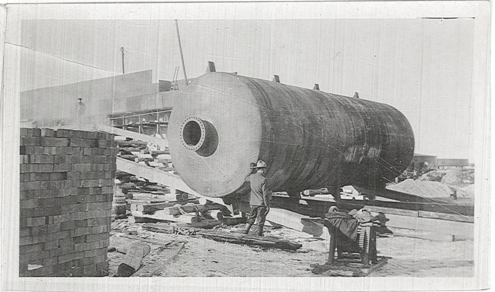 An unidentified workman stands next to a still tank.