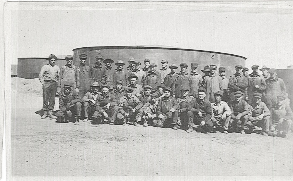 A group of men pose for a photograph in front of one of the storage tanks.