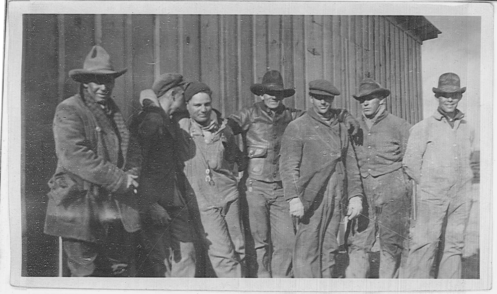 A group of men pose for the camera near one of the temporary buildings.