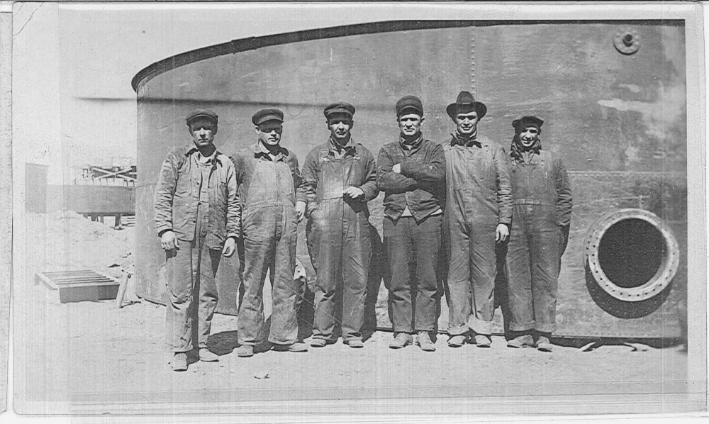 A group of men stand in front of a storage tank.
