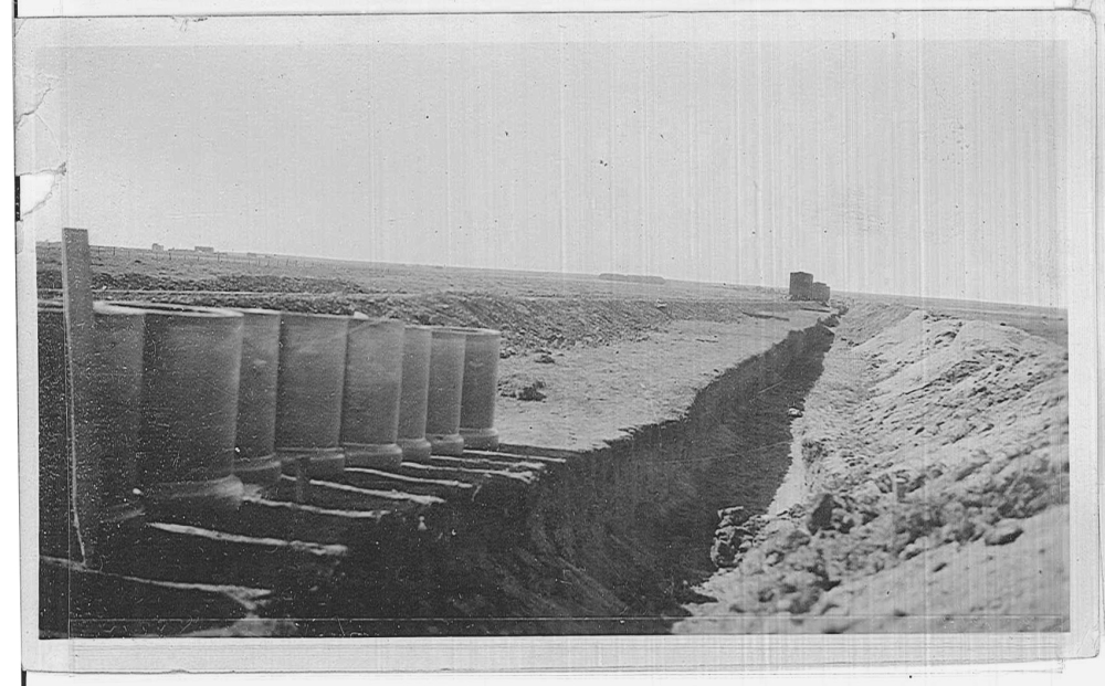 Pipes are laid out next to a trench. Note the rail cars in the distance and the rail line that was placed for the delivery of equipment.